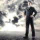 selvsikker forretningsmand på baggrund af truende skyer